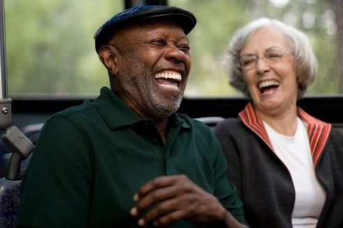 An-elderly-mixed-race-couple-sitting-on-a-bus-together-laughing